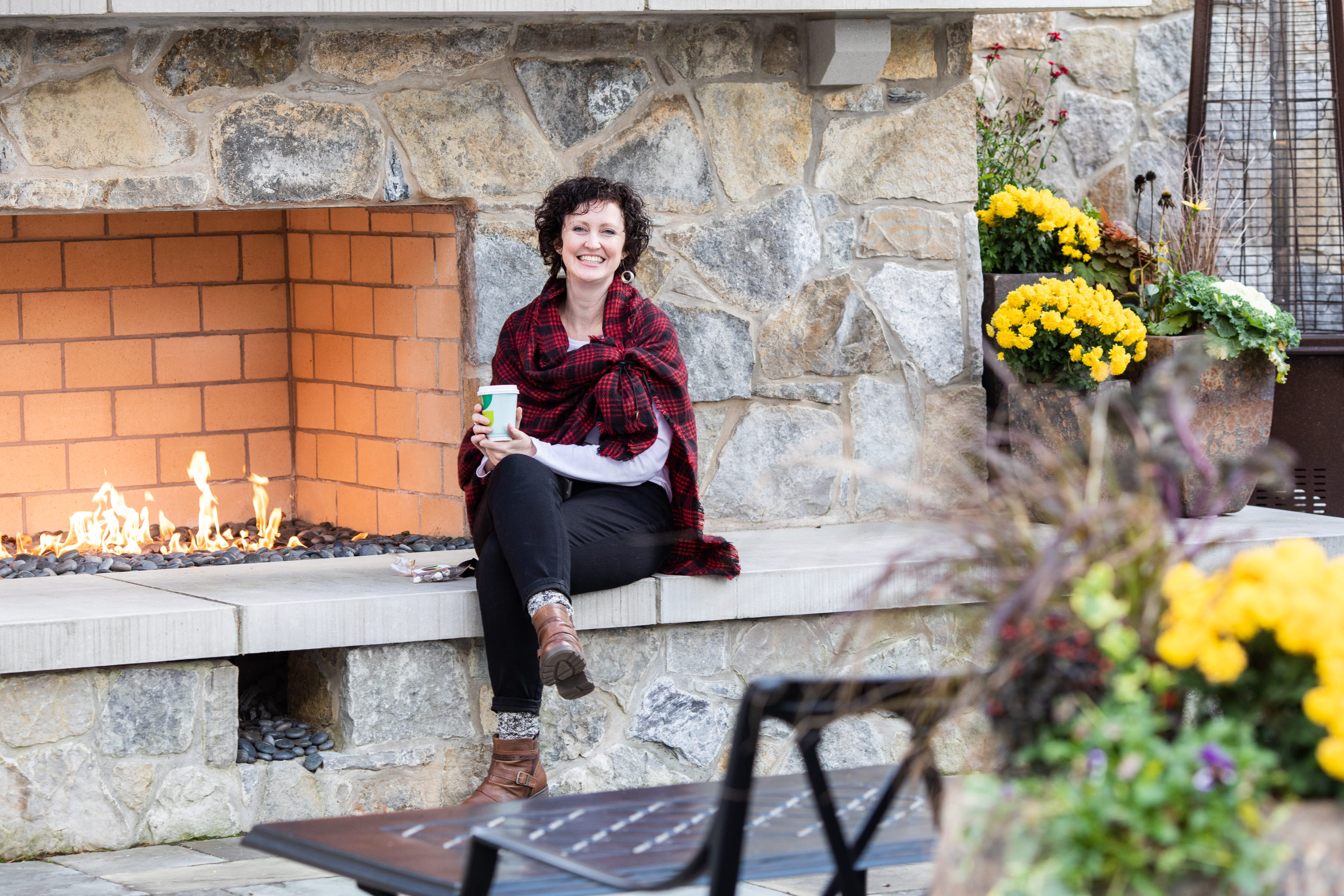 Woman sitting in front of fireplace at Leadership Center Courtyard